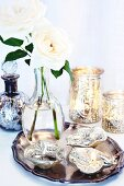 Leaf-shaped dishes and vase of white roses on silver tray