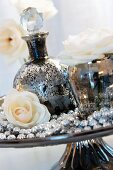 Ornamental mercury glass bottle, rose and string of beads on cake stand
