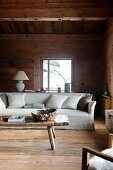 Pale, loose-covered sofa and rustic wooden coffee table in cabin living room