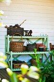 Lime green wooden shelves of gardening utensils on veranda against wooden wall