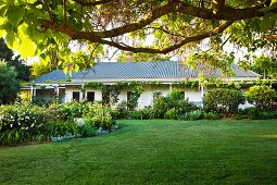 Broad lawn in front of elongated Canadian country house