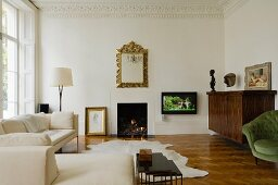 Elegant, pale living room with stucco frieze and fire in open fireplace of Victorian town house