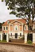 Grand, traditional manor house with closed entrance gates in London