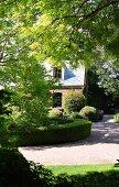 Sommerlicher Garten mit niedrigen Hecken um Beete, im Hintergrund ländliches Wohnhaus