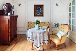 Period furniture in lounge area; Baroque-style, button-tufted armchair and sofa with curved wooden frames around delicate, round table with translucent tablecloth