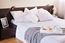 Breakfast in bed; white scatter cushions, some with ruffles, on double bed, retro table lamps on bedside cabinets integrated into dark wood headboard