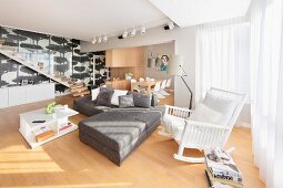 White rocking chair next to grey, modern sofa combination in open-plan interior with dining area in background