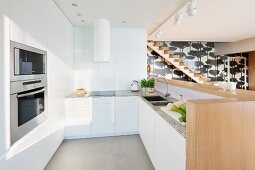 Minimalist, designer kitchen with white, flat-fronted cupboards, sink integrated into counter and fitted ovens in open-plan interior