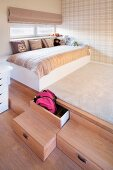 Platform with drawers in wooden steps, scatter cushions on child's bed and pale tartan wallpaper on wall
