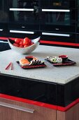 Detail of island counter with black and red accents, pale stone surface, bowl of tomatoes and two plates of sushi