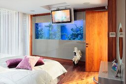 Bed with scatter cushions in shades of purple on pale blanket and aquarium integrated into wall in modern bedroom
