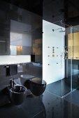 Black-tiled designer bathroom with black toilet and bidet next to glazed, floor-level shower