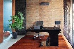 Modern, black desk with projecting top, louvre blinds on window and house plant next to glass partition in study