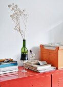 Vase made from wine glass and cut-off wine bottle, stack of books and files on red metal cabinet