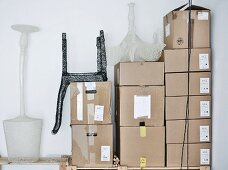 Mesh sculptures of designer lamps and chair on stacked shipping cartons in corner
