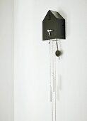 Modern, black cuckoo clock with retro-style hands
