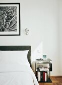 Retro-style side table next to bed with grey upholstered headboard and Tolomeo lamp on wall next to framed drawing