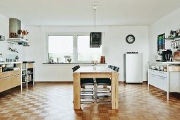 Dining area with wooden table and cantilever chairs and kitchen counter elements along side walls in minimalist kitchen with mosaic parquet floor