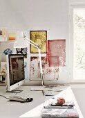 Desk with table lamp and computer below painted fabrics on wall