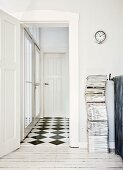 Stack of magazines next to open door and view into hallway with chequered floor in traditional interior