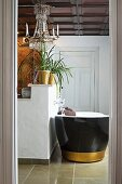 Free-standing bathtub with black outside and gold stripe seen through open door