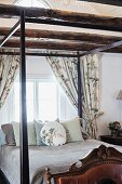 Scatter cushions arranged on dark, wooden four-poster bed below window in bedroom with wood-beamed ceiling