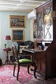 Antique chair with green-upholstered seat at Biedermeier cabinet with pull-out writing desk in rustic living room