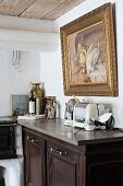 Retro electrical appliances on top of half-height kitchen cabinet made from dark wood below gilt-framed picture