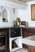 Old masonry kitchen cooker with firewood store integrated into kitchen counter below arched niche in wall