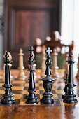 Old chess pieces made from carved, black-painted wood on chessboard