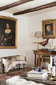 Candlesticks on ottoman opposite bench with animal-skin rug below gilt-framed portrait of woman on wall