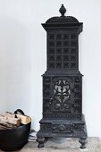 Antique, cast iron, wood-burning stove against white wall