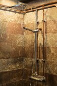 Modern shower head, tap fittings and exposed copper piping on brown marbled wall tiles