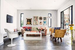 Eclectic, minimalist interior with concrete floor, white retro plastic chair, wooden shell armchairs and colourful around modern coffee table