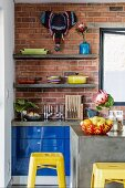 Detail of concrete counter and retro, yellow bar stools in front of kitchen counter with blue fronts against brick wall