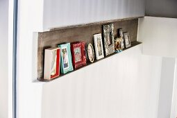 Framed pictures on narrow shelf formed by recess in wall