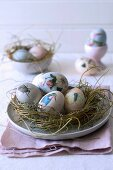Easter eggs decorated with animal motifs in straw nest