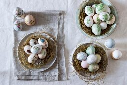 Still-life arrangement of Easter nests and painted eggs in egg cups