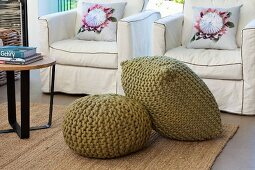 Olive-green pouffes in front of armchairs with washable loose covers and scatter cushions with floral motifs