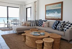 Rattan coffee table with matching stools of various sizes and modern corner sofa in open-plan interior; dining area in front of panoramic window in background