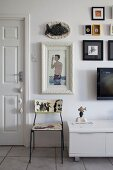 Delicate chair with painted backrest and seat next to sideboard below gallery of framed pictures on wall