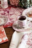 Crockery and table linen with red toile de jouy patterns on rustic wooden table