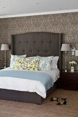 Box spring bed with tall headboard and elegant table lamps on bedside cabinets against brocade-patterned wallpaper