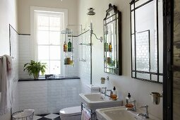 Twin washstands below framed mirrors on wall; shower area next to window with white wall tiles in background