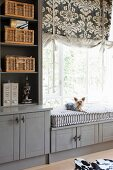 Custom, fitted, grey-painted cabinets, shelving and window seat with small dog sitting on cushion below Roman blind with ornamental pattern