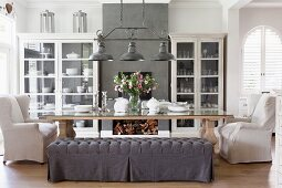 Comfortable dining area with upholstered chairs and bench with grey, loose covers below vintage pendant lamps with metal lampshades