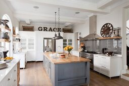 Spacious, open-plan kitchen; central counter with wooden worksurface on grey-painted base unit