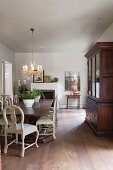 Elegant dining room with antique, country-house-style furniture and chandelier