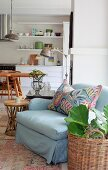 Pale blue armchair with colourful scatter cushion and house plant in wicker basket on floor; dining area in open-plan kitchen in background