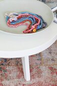 Necklaces of different colours in white dish on coffee table